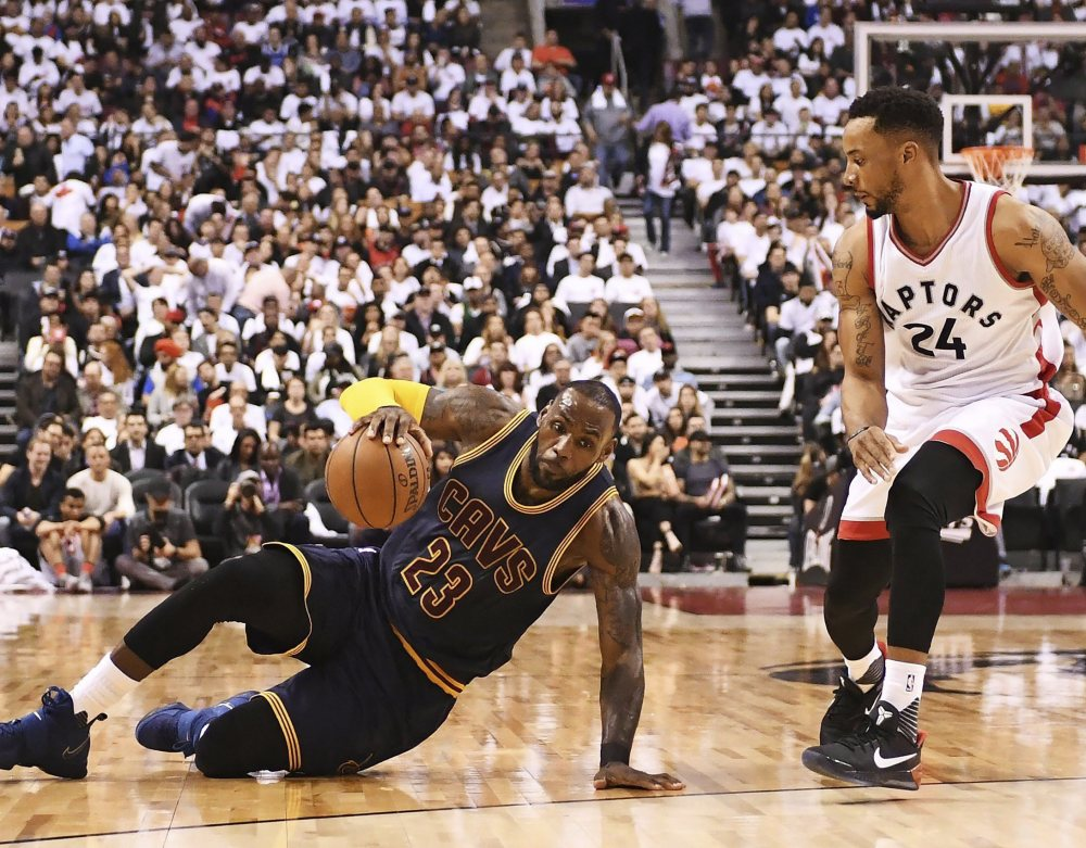 Cavaliers forward LeBron James slips on the floor as Raptors guard Norman Powell looks on during Friday's second half.