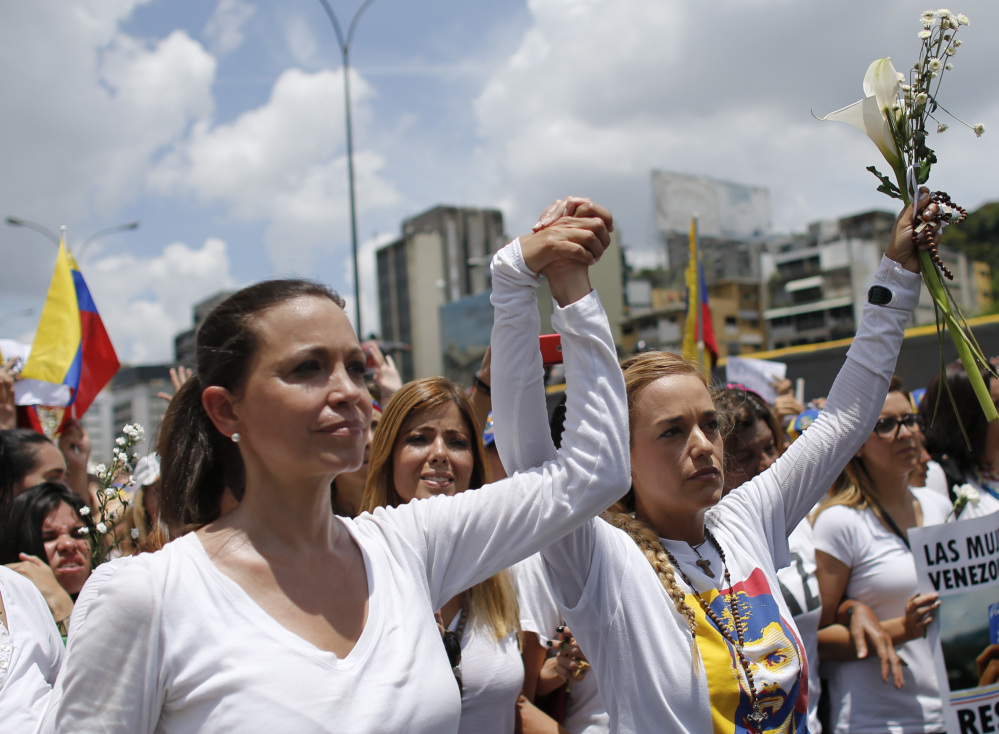 Opposition leader Maria Corina Machado, left, and Lilian Tintori, wife of jailed opposition leader Leopoldo Lopez, lead a women's march in Caracas on Saturday.