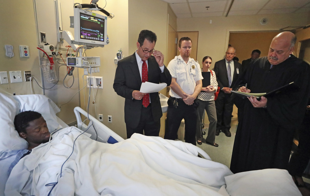 At Tufts Medical Center in Boston, prosecutor John Pappas, second from left, reads as Judge Michael Bolden, right, takes notes during the arraignment of Bampumim Teixeira, who lies in a hospital bed Monday. Teixeira is accused of murdering two engaged doctors in their South Boston penthouse condominium.