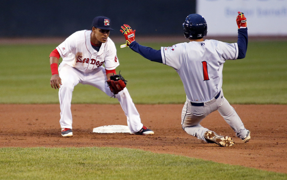 Deiner Lopez of the Portland Sea Dogs waits to apply the tag as Jio Mier of the Binghamton Rumble Ponies is caught attempting to steal second.