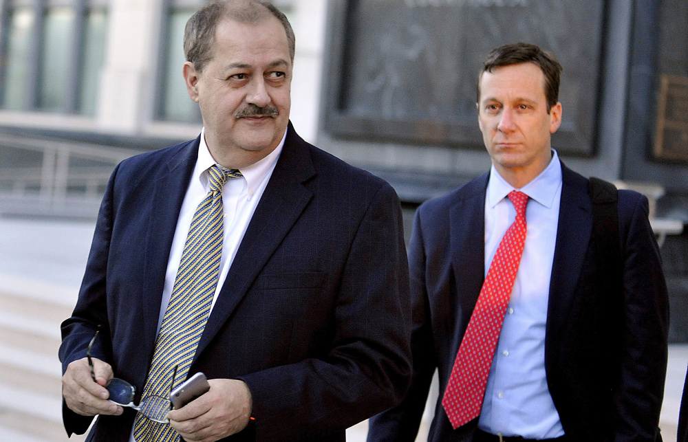 Former Massey Energy CEO Don Blankenship, left, walks out of the courthouse after the jury deliberated for a fifth full day in his trial in 2015 in Charleston, W. Va. After his release from a halfway house in Phoenix Wednesday, he must serve a year of supervised release.