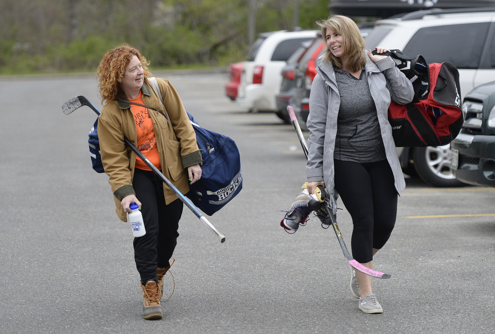 Sally Morris and Jill Piker head into Family Ice Center in Falmouth last week to play with the Morning Hockey Society. There are no officials, no coaches and generally no fans, but there is plenty of social time and exercise, members say.