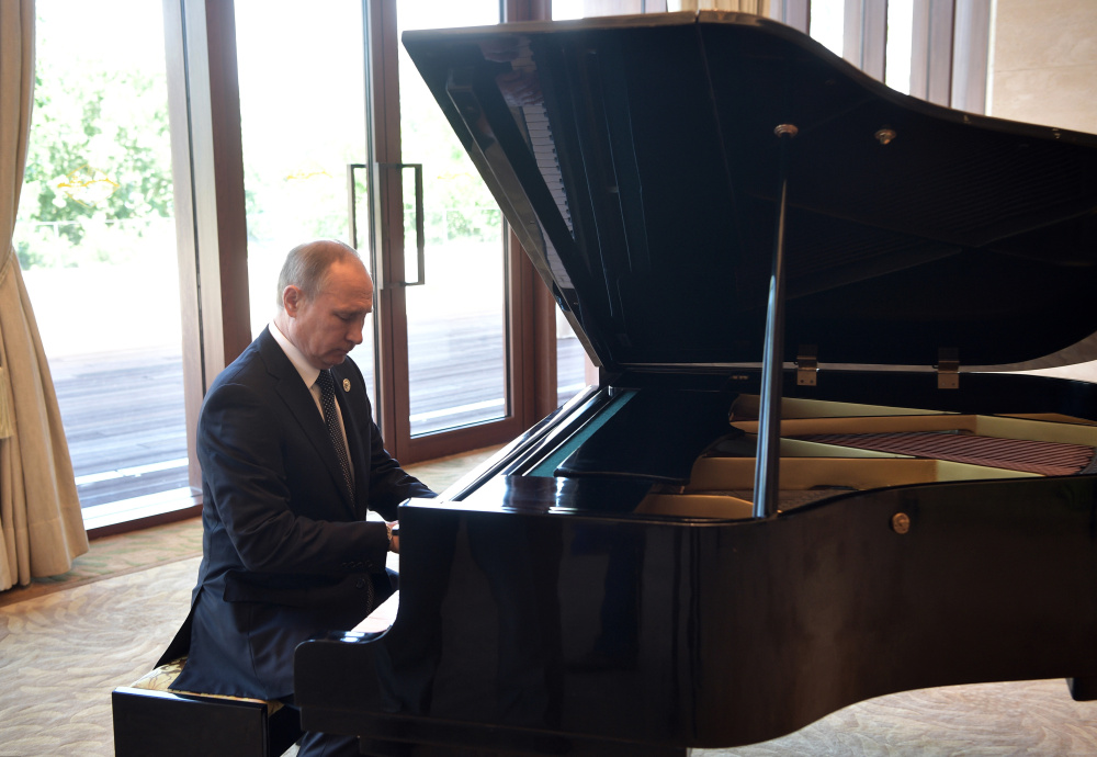 Russian President Vladimir Putin plays piano before his talks with Chinese President Xi Jinping prior to the opening ceremony of the Belt and Road Forum in Beijing on Sunday.