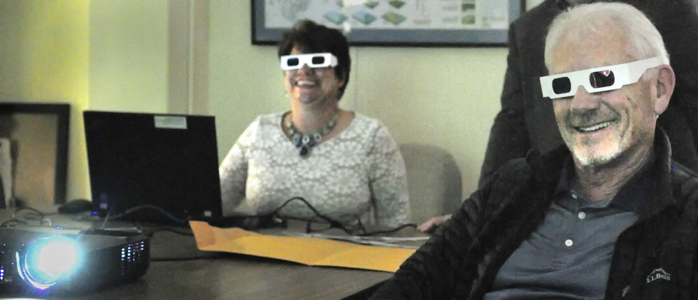 Jennifer Dube of Friends of the Maine State Museum and sportsman Paul Wade try out glasses for watching stereoview photos showing Maine's hunting, trapping and fishing history. There will be a presentation of the photos Saturday at the Elks Lodge in Augusta.