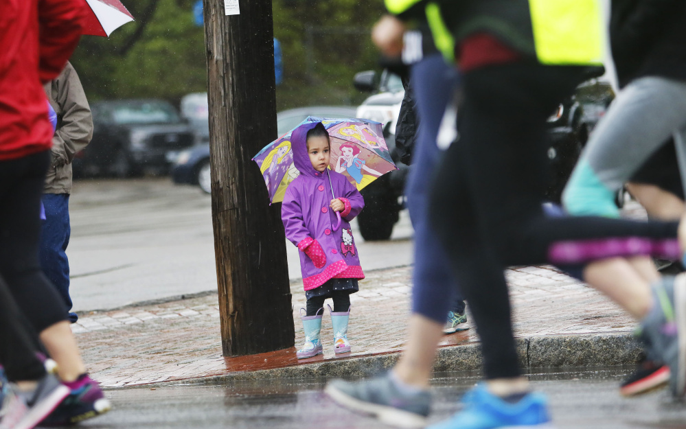 Bella Laflin, 3, of Biddeford holds a princess umbrella while watching runners' legs pass by at the start of the Mother's Day 5K in Portland. Bella was with her mom, Erin Laflin, and grandfather, Kirk Laflin of South Portland to see her dad, Derek, running in the race.