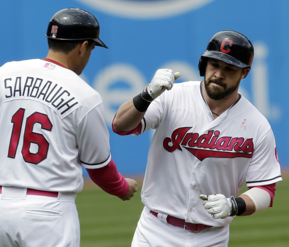 Cleveland's Jason Kipnis, right, is congratulated by third base coach Mike Sarbaugh after hitting one of his two home runs Sunday in the Indians' 8-3 win.