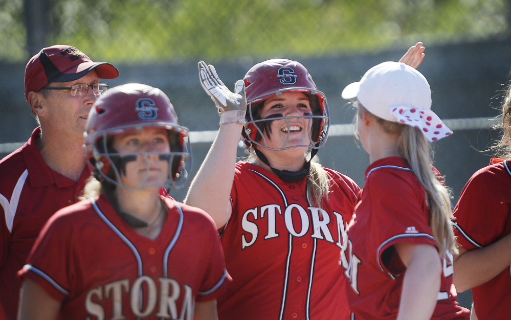 Abbie Murrell of Scarborough receives congratulations Tuesday after lining a home run during a 15-0, five-inning victory at Windham. Murrell finished with five RBI and, on top of that, allowed one hit in four innings in a game against an undefeated opponent.