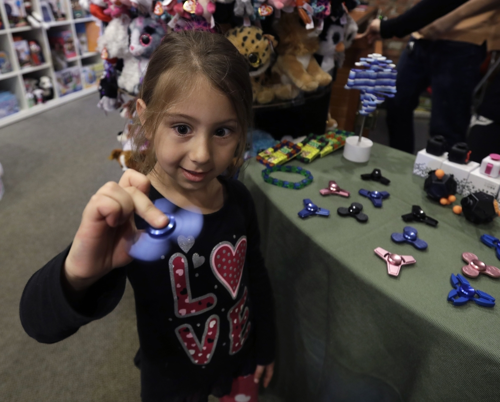 Penelope Daversa, 4, plays with a fidget spinner at the Funky Monkey Toys store in Oxford, Mich. Many stores are having a hard time keeping them in stock and parents are going crazy trying to find them.