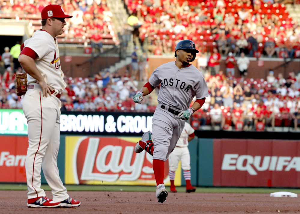 Boston's Mookie Betts rounds the bases past Cardinals third baseman Jedd Gyorko after hitting a home run to open Tuesday's game at St. Louis.