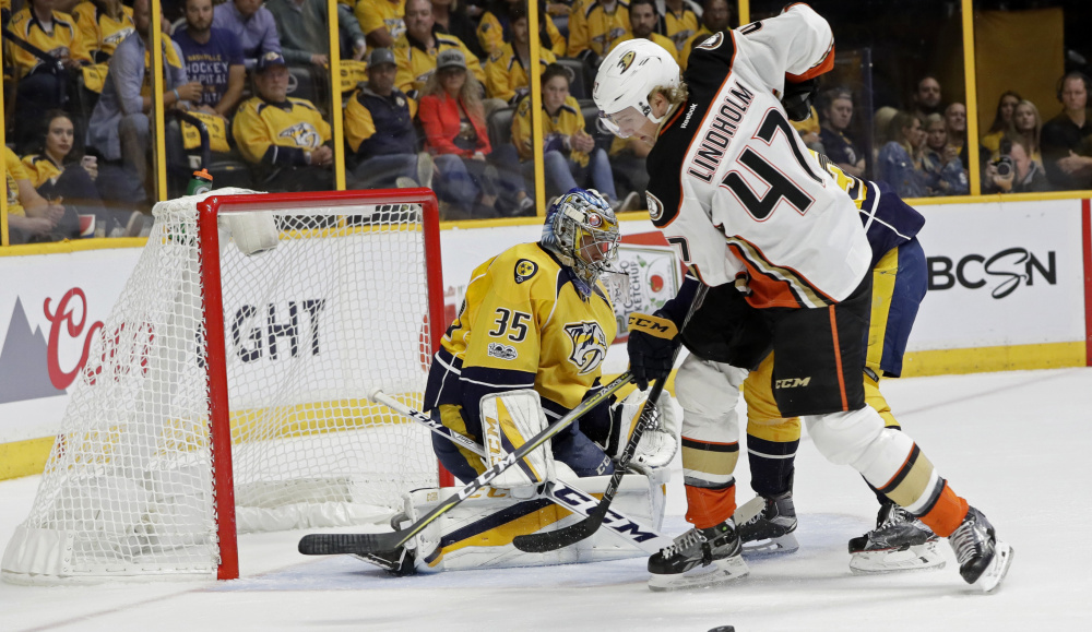 Hampus Lindholm of the Anaheim Ducks attempts to control the puck in front of Nashville goalie Pekka Rinne during the first period of Nashville's 2-1 victory Tuesday night in Game 3 of the Western Conference finals.