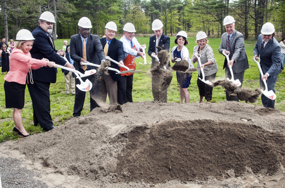 Dignitaries toss a ceremonial shovel of dirt at the Cabin in the Woods groundbreaking on Friday at VA Maine Healthcare Systems-Togus.