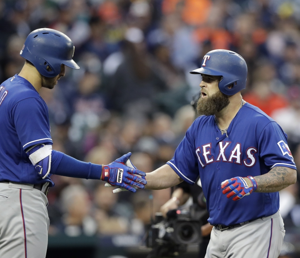 The Rangers' Mike Napoli, right, is greeted by teammate Joey Gallo after hitting a solo home run during a 5-3 win over the Tigers on Friday night in Detroit.
