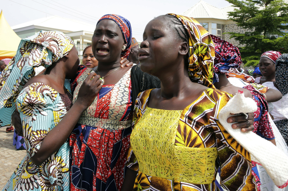 Family members react as they embrace a relative, one of the released kidnapped schoolgirls, in Abuja, Nigeria, Saturday,