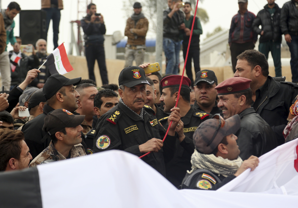 Lt. Gen. Abdul-Wahab al-Saadi of Iraq's special forces, center, prepares to raise a national flag during a parade to celebrate the eastern side of Mosul being fully liberated in January.