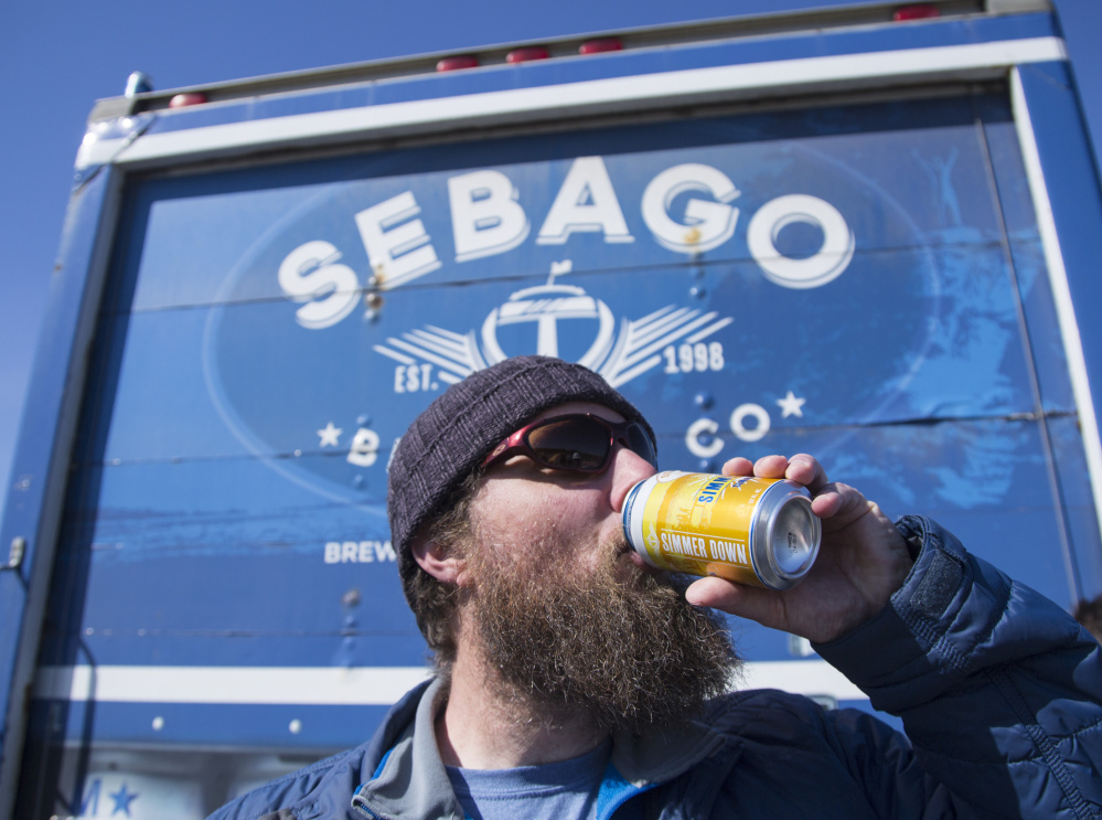 Tom Abercrombie, a brewmaster at Sebago Brewing Co., takes a celebratory sip of Simmer Down, its summer ale, at a groundbreaking event last month for the brewery's new headquarters in Gorham. After two years of double-digit growth, Sebago plans to double the size of its brewery and tasting room, hoping to draw fans off the beaten path.