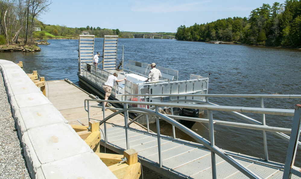 Swan Island staffers push the ferry off from the new dock on the shore of the Kennebec River in Richmond.