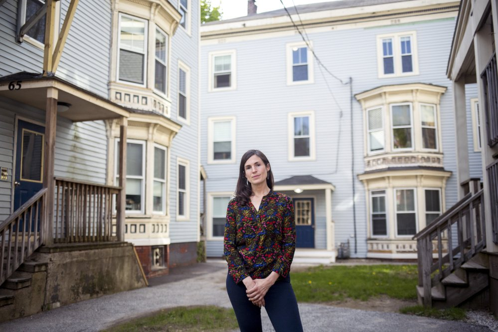 Bre Chamberlain, a member of a group pursuing tenant protections in Portland, stands in front of the Parkside apartments where tenants faced mass evictions in 2016.