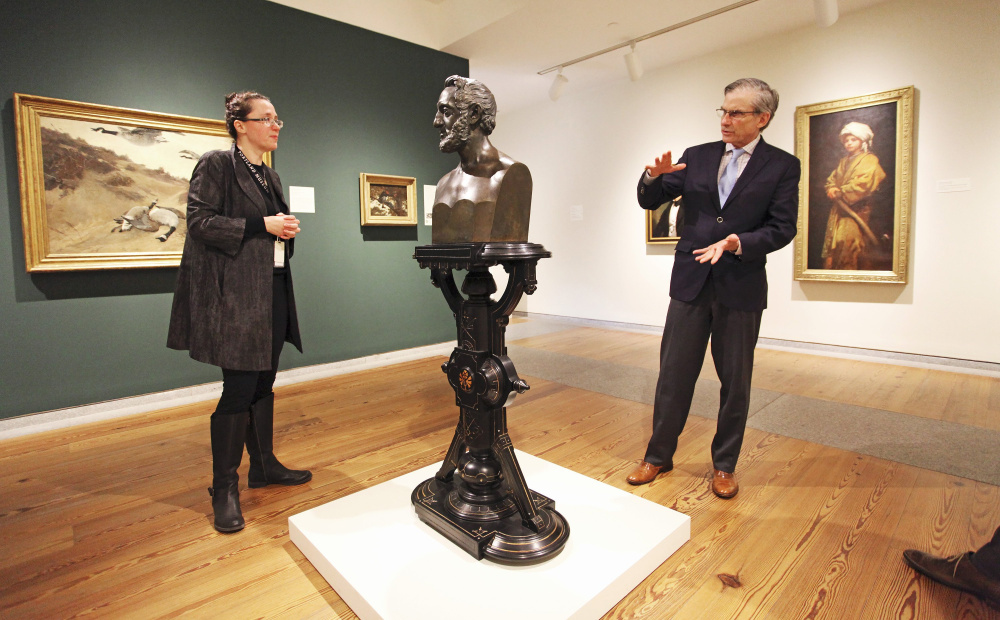 """William """"Bro"""" Adams, right, who this week stepped down as chairman of the National Endowment for the Humanities, discusses a sculpture pedestal of Dr. John Mofatt, 1852, while visiting the Friedman Gallery with Jessica May, chief museum curator, during a tour of the Portland Museum of Art in March. The 69-year-old said he did not have specific plans for his post-NEH career."""