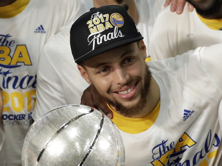 The Warriors' Stephen Curry poses by the trophy after Golden State beat the Spurs 129-115 Monday to finish a sweep of the West finals.