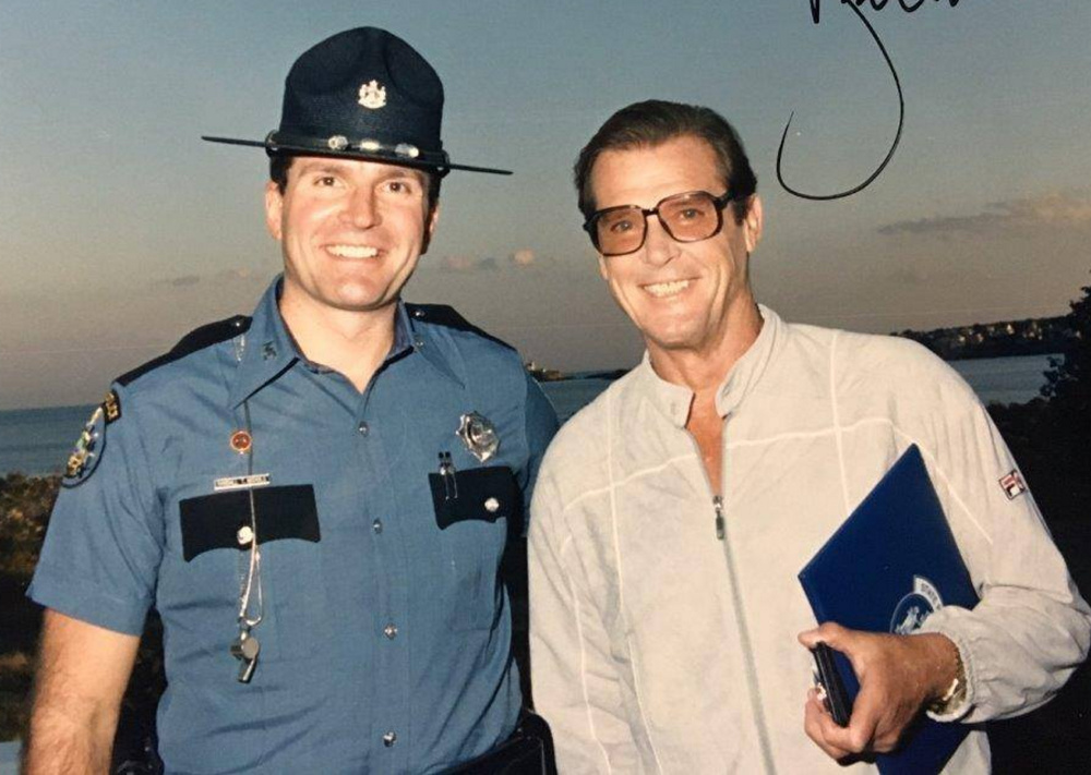 Randy Nichols and Roger Moore pose in 1989 after Moore was named an honorary state police captain.