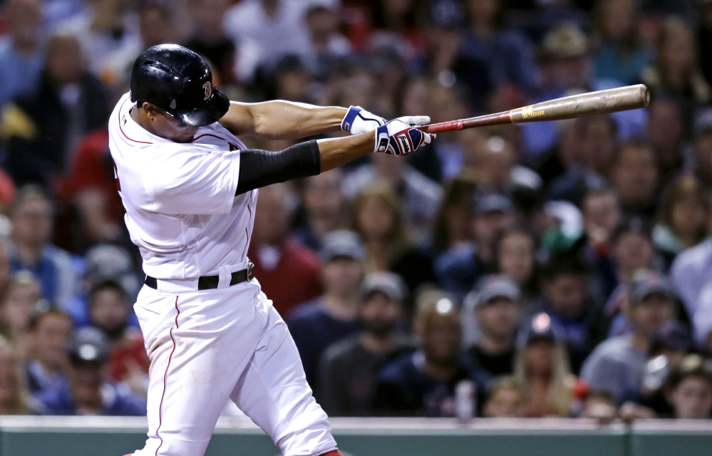 Boston's Xander Bogaerts follows through on his two-RBI single during the fifth inning Tuesday against the Texas Rangers at Fenway Park in Boston.