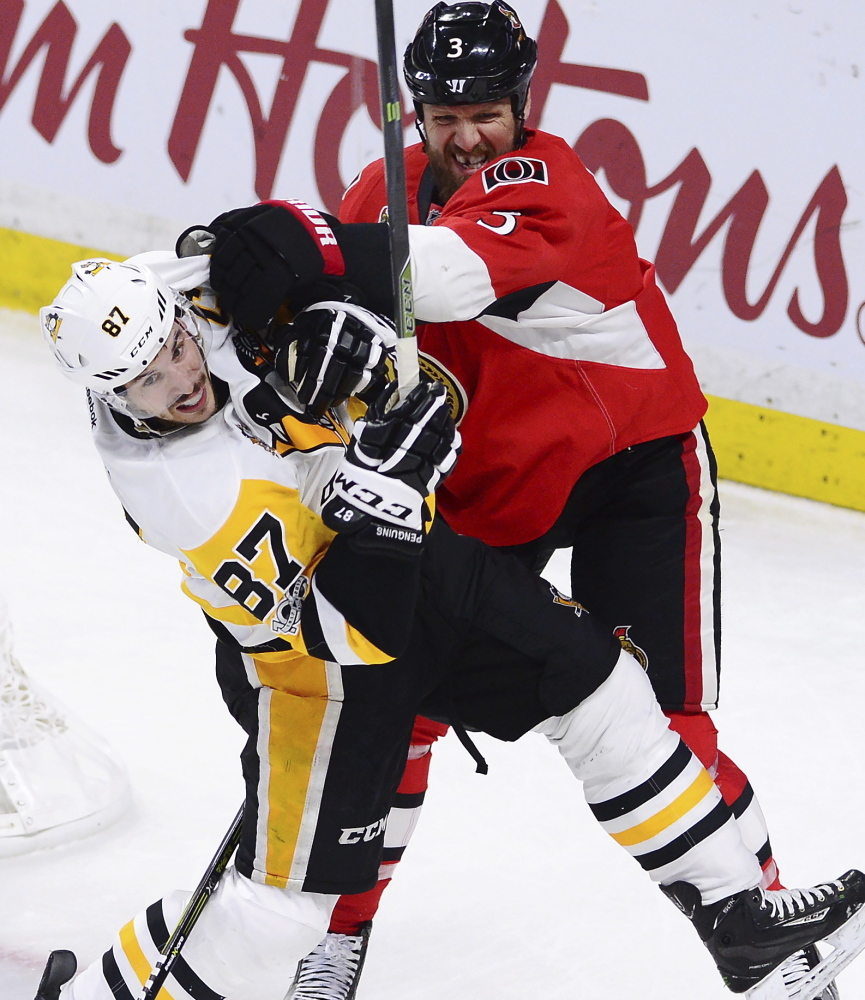 Pittsburgh center Sidney Crosby, left, takes a shove from Ottawa defenseman Marc Methot during Game 6 in Ottawa, Ontario, on Tuesday night. The Senators won, 2-1.