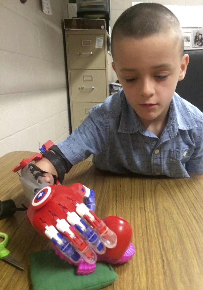 Harun Halilovic, a second grader in Bedford, N.H., grabs an object with a prosthetic arm 3-D printed for him by students at the Academy for Science and Design in Nashua, N.H. He hopes to be able to catch a ball and ride a bike.