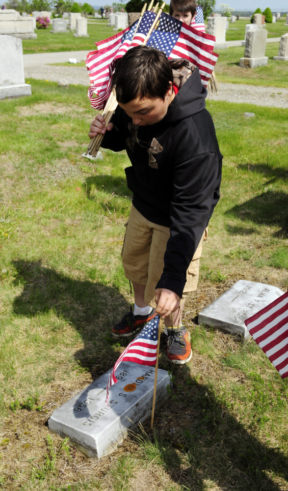 Brody Sanborn places a flag next to a veteran's grave Wednesday in Mount Hope Cemetery in Augusta. Whitefield students helped place flags on veterans' graves in the section near the Augusta State Airport.
