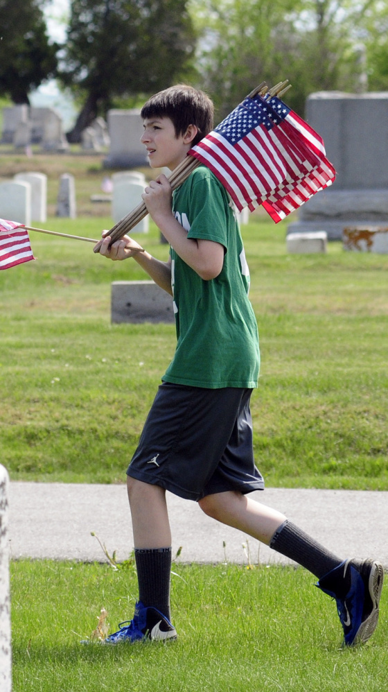 Colin Dalton searches for a veteran's grave in Augusta. Whitefield students placed flags in the section near the Augusta State Airport.