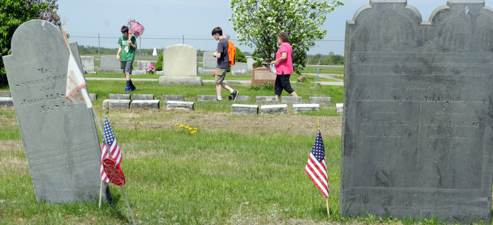Volunteers look for veterans' graves Wednesday in Mount Hope Cemetery in Augusta.