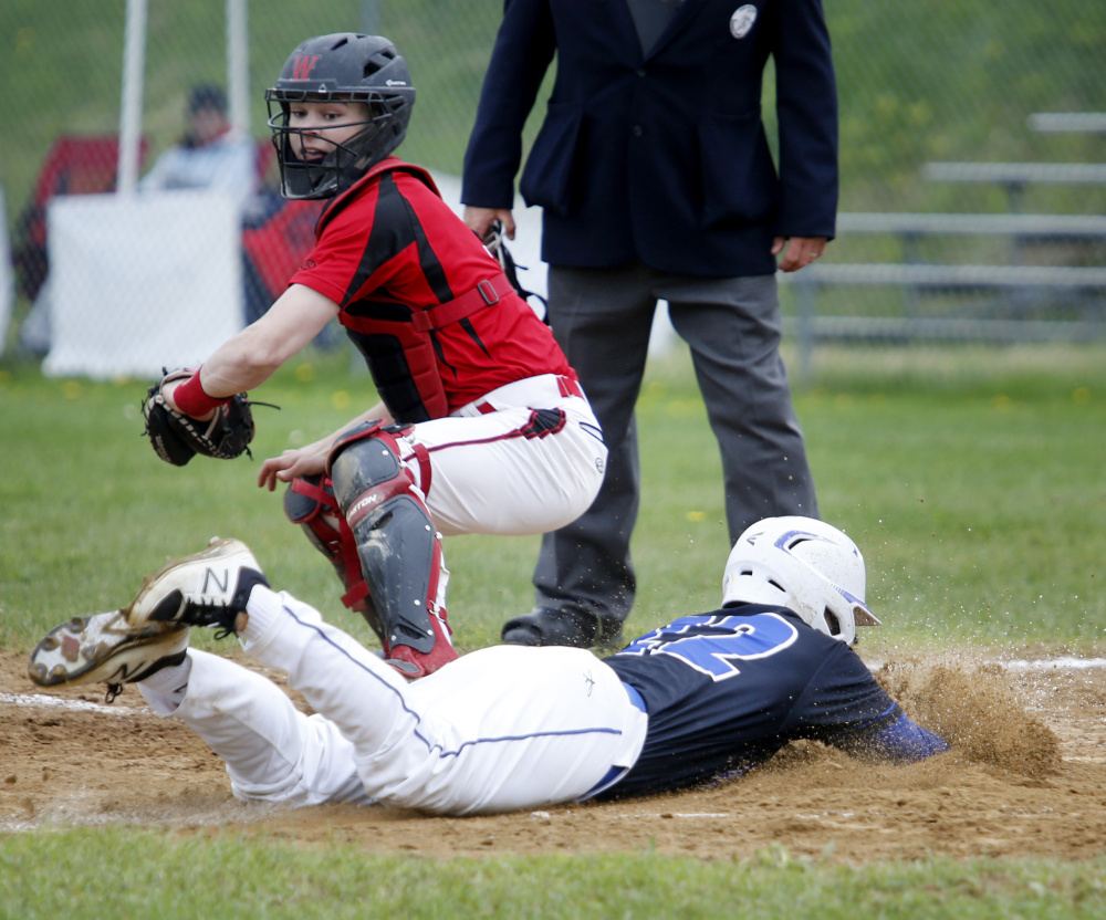 Colin Coyne of Falmouth dives across the plate to score a run in the third inning Thursday as Wells catcher Michael Wrigley fields the late throw. Falmouth won, 5-4.