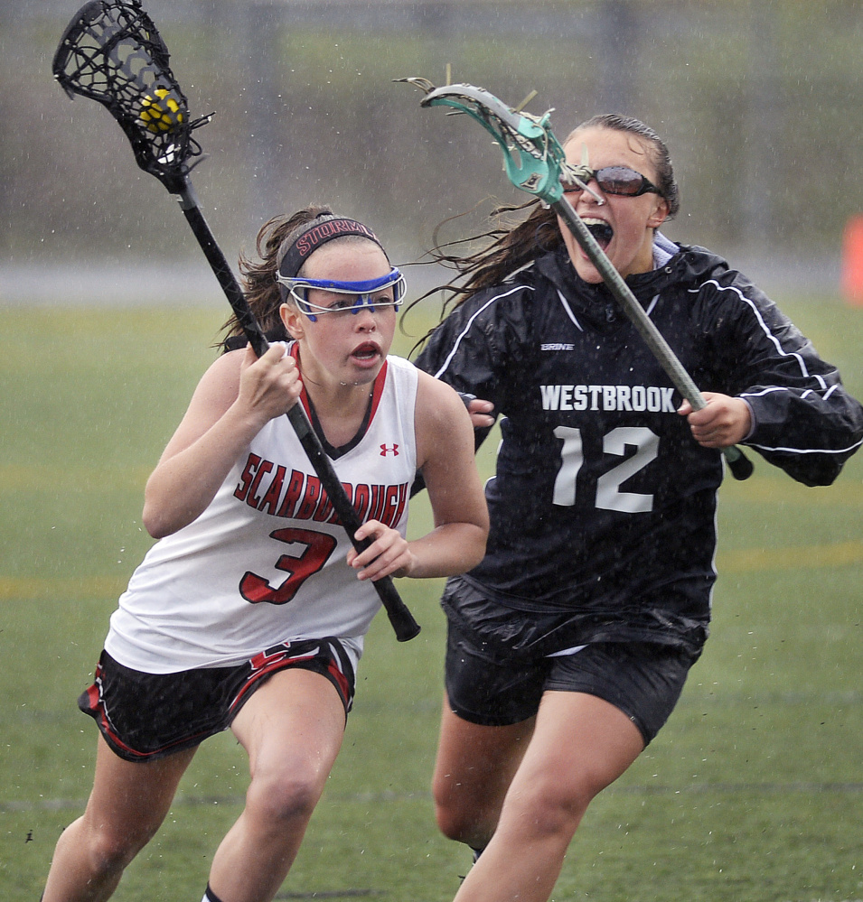 Scarborough's Sam Brodeur is chased by Westbrook's Alexis Witham during their girls' lacrosse match Thursday in Scarborough. Scarborough won, 19-10.