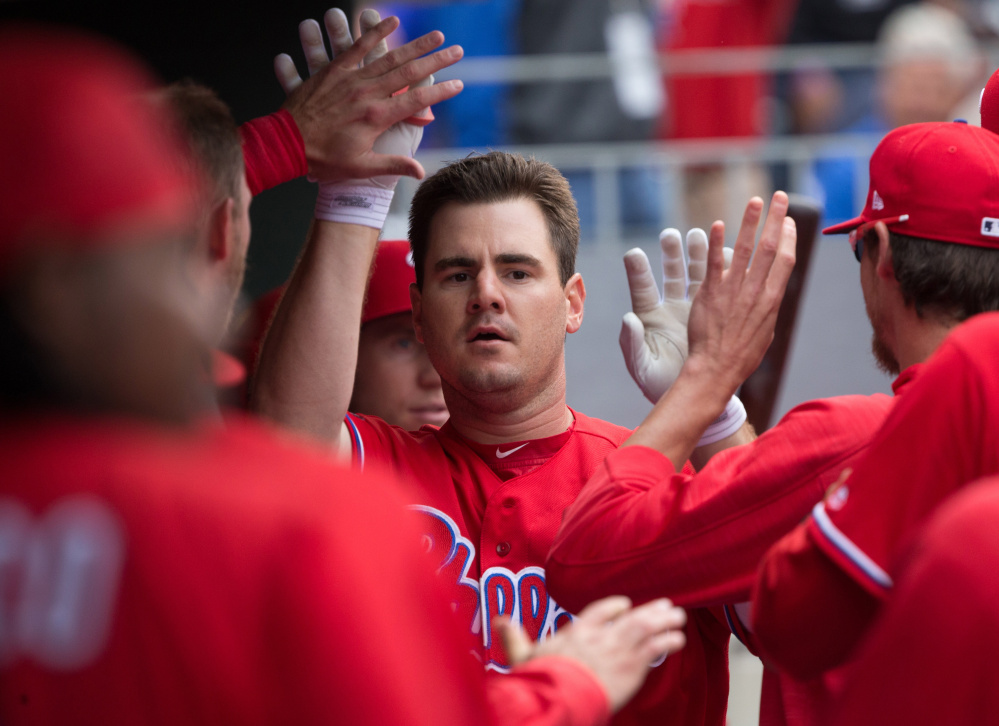 Tommy Joseph of the Phillies is welcomed by teammates Thursday after hitting a tying home run in the seventh inning against the Rockies. He also singled home the winner in the 11th.