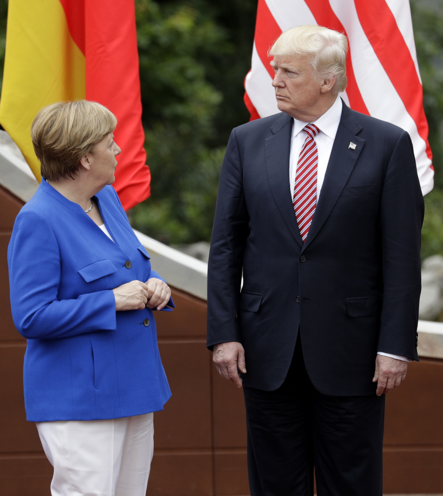 German Chancellor Angela Merkel speaks with President Trump during a group photo at the G-7 summit in the Ancient Theatre of Taormina in the Sicilian citadel of Taormina, Italy, on Friday. In January, Trump said that German car manufacturers like BMW could face U.S. tariffs of up to 35 percent if they set up plants in Mexico instead of in the U.S. and try to export the cars to the U.S.