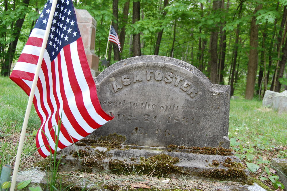 In this Wednesday, May 24, 2017 photo, an American flag stands at the grave of Asa Foster, at a Canterbury, N.H., cemetery. Foster, who enlisted in the Continental Army on July 4, 1780, at age 15, and was under Gen. Benedict Arnold's command.  Canterbury recently finished a yearlong project recording the veterans buried in its 34 cemeteries, from the pre-Revolutionary War era to Vietnam. (John Goegel via AP)