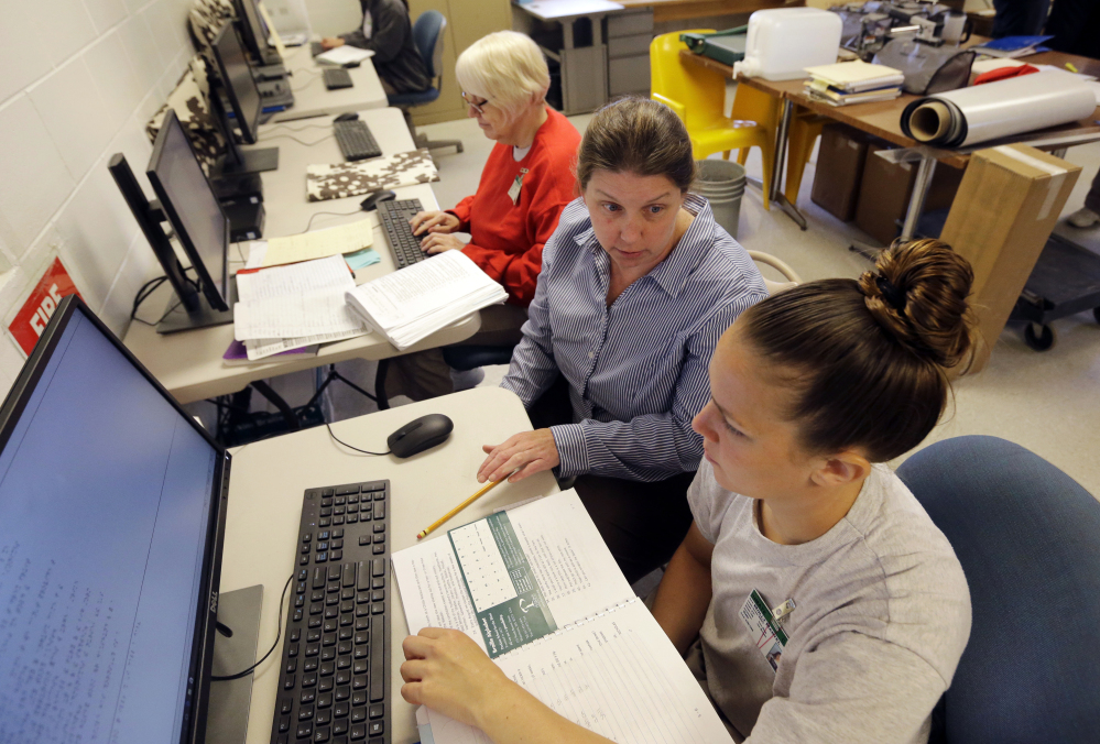 Inmates Linda Ellis, left, and Molly Martel, right, use computers Monday as they receive instruction from Nancy Wittmershaus, center, at the New Hampshire Correctional Facility for Women in Goffstown, N.H. The women are participating in an innovative program to learn how to translate books into Braille.