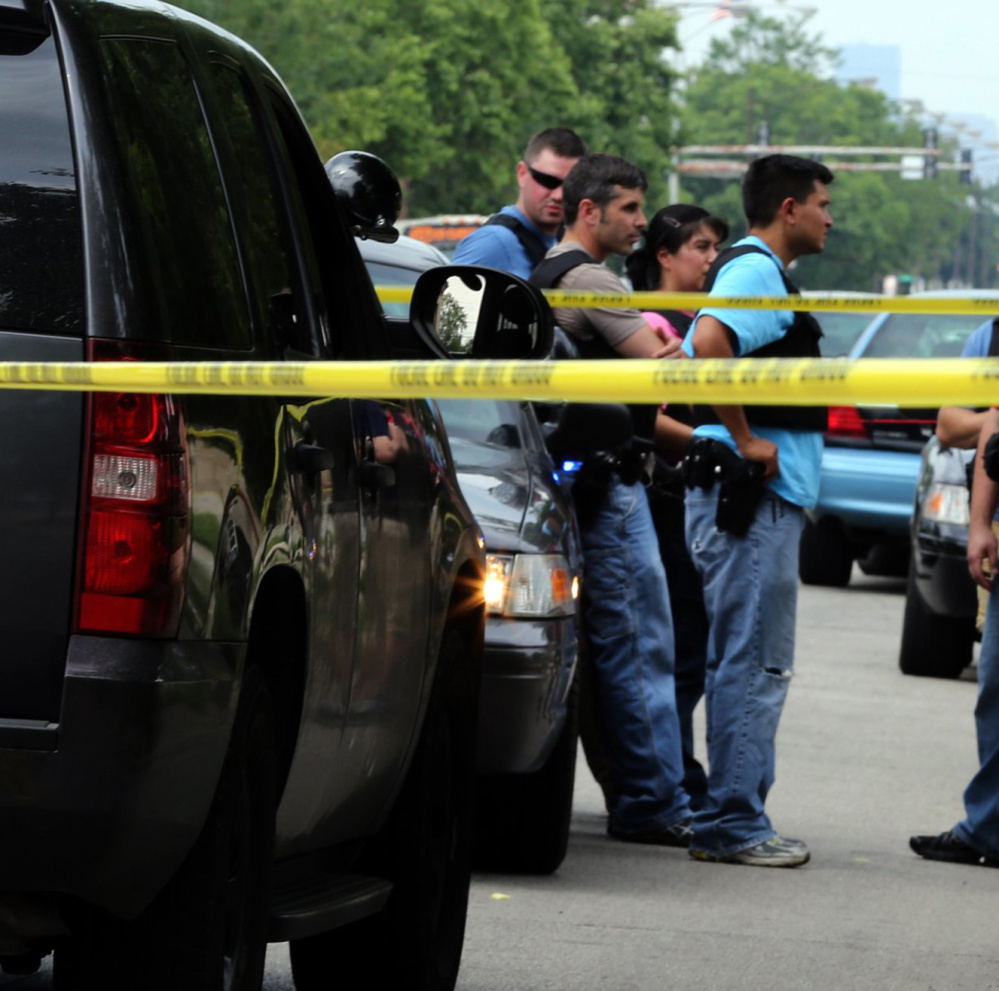 Officers at a 2013 police-involved shooting in Chicago. New research indicates that states with stricter gun laws have fewer fatal shootings of civilians by police. Officers investigate the scene of the police-involved shooting of Christian Green, 17, in the 5600 block of South State State on July 4, 2013 in Chicago, Ill. Fatal shootings of civilians by police officers are less common in states with stricter gun laws than in states that take a more relaxed approach, a new research says. (