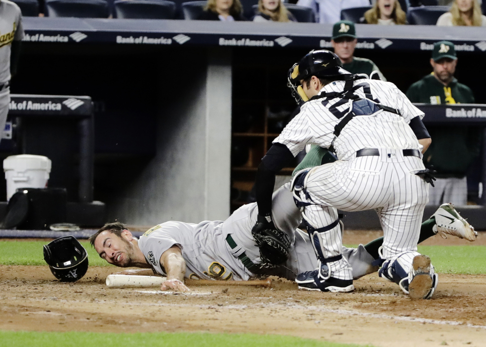 Catcher Austin Romine of the New York Yankees tags out Adam Rosales of the Oakland Athletics during the eighth inning of Oakland's 4-1 victory Friday night at Yankee Stadium.