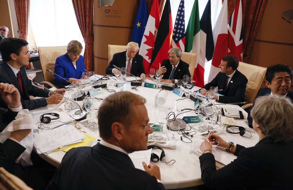 From left, Canadian Prime Minister Justin Trudeau, German Chancellor Angela Merkel, President Trump, Italian Prime Minister Paolo Gentiloni, French President Emmanuel Macron, Japanese Prime Minister Shinzo Abe, British Prime Minister Theresa May, European Council President Donald Tusk and European Commission President Jean-Claude Juncker (unseen) sit around a table during the G7 Summit in Taormina, Sicily, Italy, Friday.