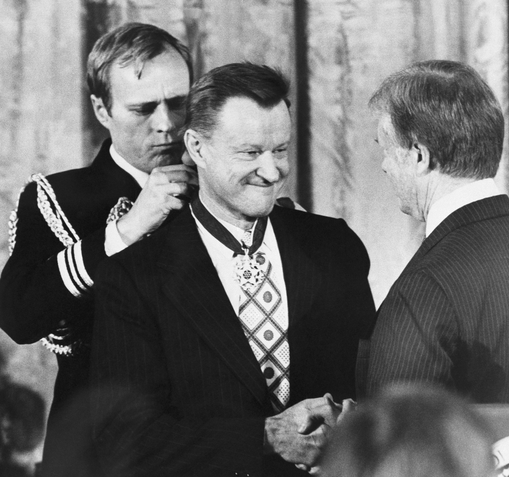 Zbigniew Brzezinski shakes hands with President Jimmy Carter as Carter presents him with the Medal of Freedom. Brzezinski, Carter's national security adviser and who helped write the Camp David accords, died Friday at age 89.
