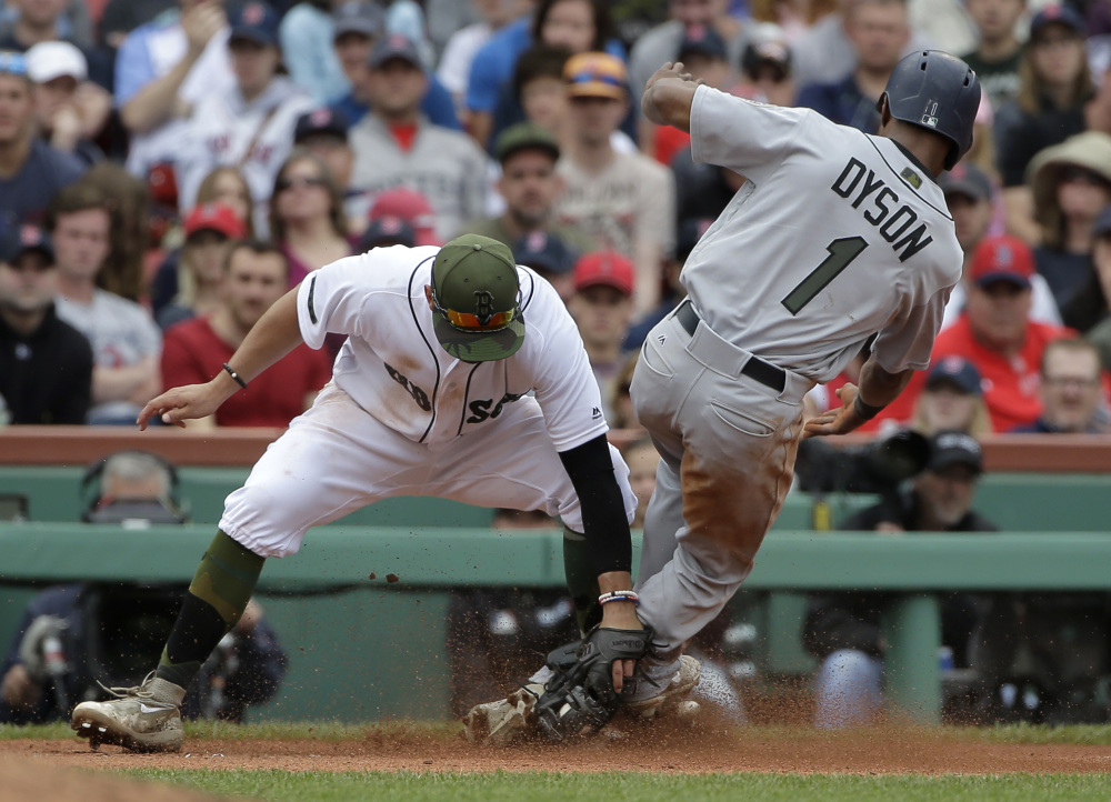 Seattle's Jarrod Dyson slides while attempting to steal third base as Boston's Deven Marrero makes the tag in the eighth inning Sunday at Fenway Park in Boston.