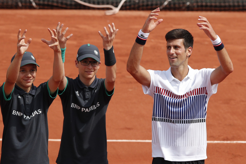 Defending French Open champion Novak Djokovic celebrates with a couple of ball boys after his 6-3, 6-4, 6-2 win over Marcel Granollers in a first-round match Monday.