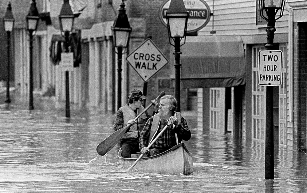 "Sumner ""Sam"" Webber, left, and John Jacques paddle a canoe on Water Street just past Central Street after the Kennebec River flooded downtown Hallowell in 1987."
