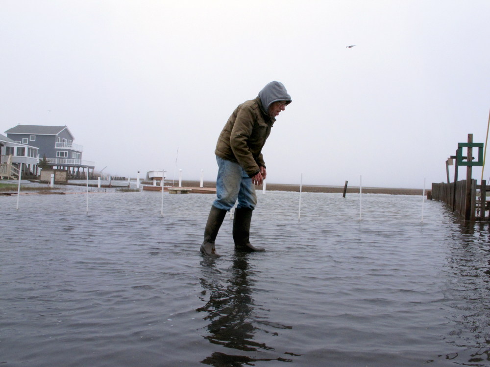 Jim O'Neill walks through a flooded street in front of his home in Manahawkin N.J., after a moderate storm in April. He lives in a low-lying area near the Jersey shore, and is often affected by back-bay flooding, a type of recurring nuisance flooding that's affecting millions of Americans.