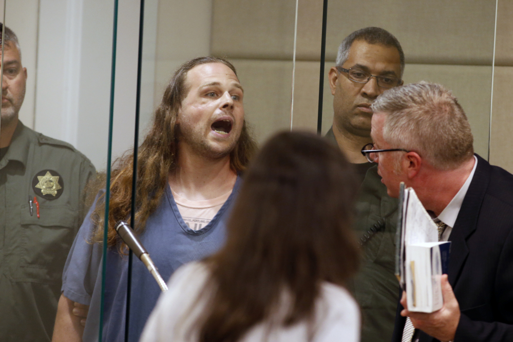 Jeremy Joseph Christian, accused of fatally stabbing two men who came to the aid of two young women he was verbally abusing, shouts as he makes his initial court appearance in Multnomah County Circuit Court in Portland, Ore., Tuesday. At left, a sidewalk  memorial at the stabbing site.