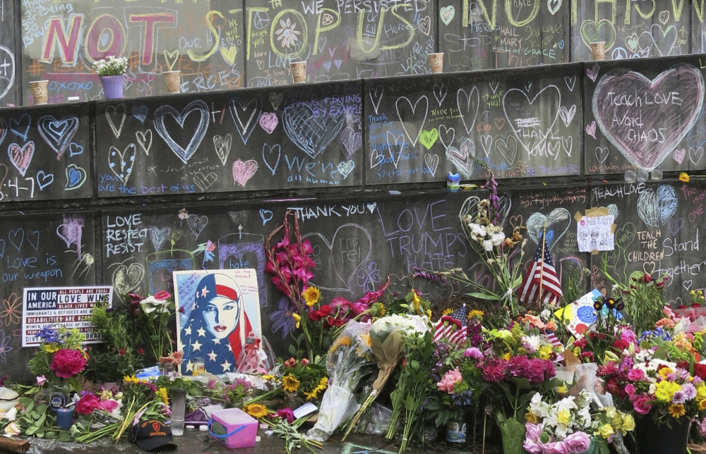 Flowers, candles and chalk tributes are seen on Tuesday, May 30, 2017, covering a memorial to two men who were fatally stabbed after shielding two young women from an anti-Muslim tirade on a Portland, Ore., light-rail train. Jeremy Joseph Christian, 35, made a first court appearance on charges of aggravated murder and attempted murder Tuesday in a Portland, Oregon courthouse. (AP Photo/Gillian Flaccus)
