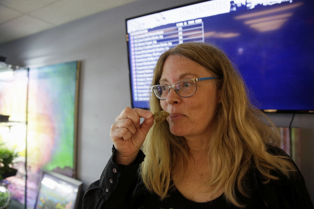 Debby Goldsberry, executive director, smells a hybrid bud at the Magnolia Wellness marijuana dispensary in Oakland, Calif.