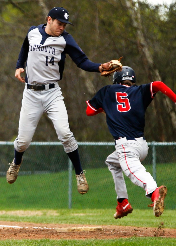 Yarmouth first baseman John Thoma tags Gray-New Gloucester's Jacob Winchester while leaping for a high throw.