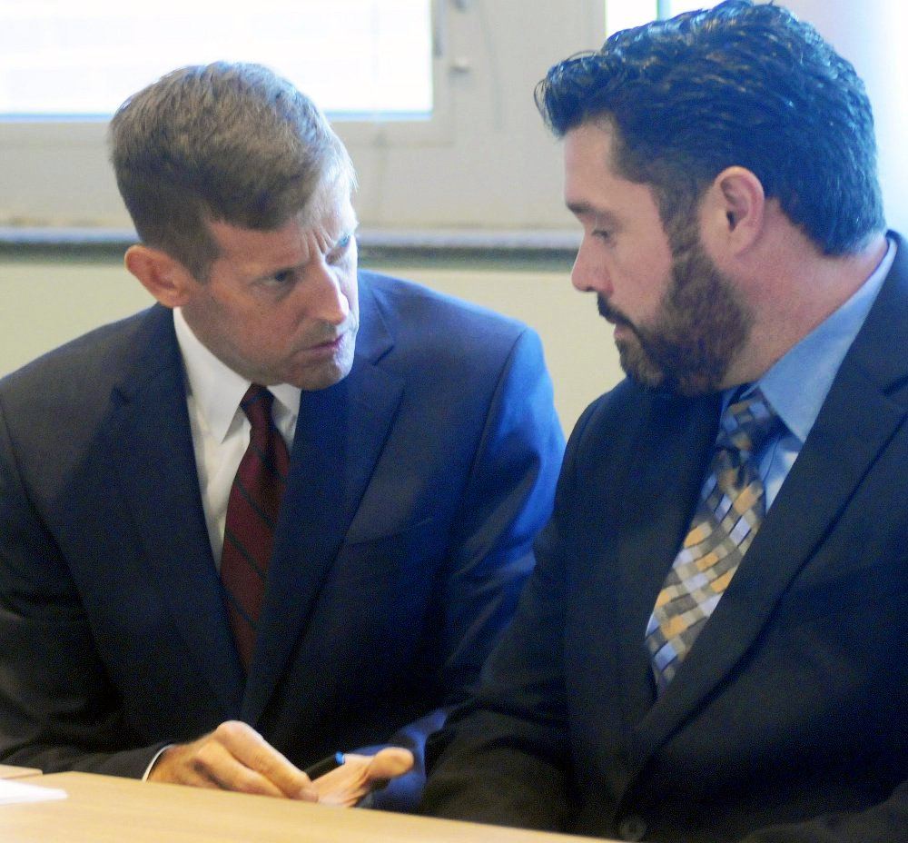 Bryan Carrier, right, and his attorney, Walt McKee, confer during a hearing Sept. 26 in Augusta at the Bureau of Motor Vehicles.