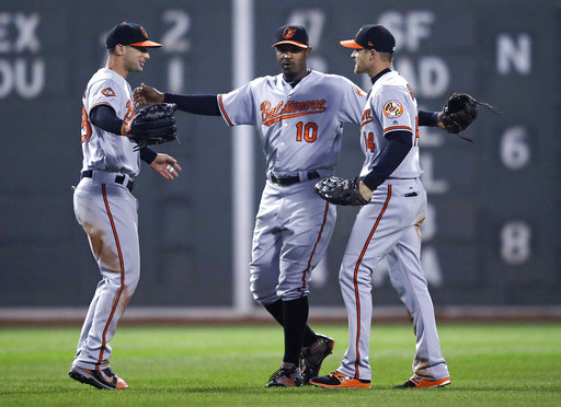 Baltimore center fielder Adam Jones celebrates with right fielder Craig Gentry, right, and left fielder Joey Rickard left, after defeating the Boston Red Sox 5-2 Monday.  Associated Press/Charles Krupa